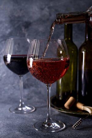 Rotwein. Flasche und Glas Rotwein. Vintage-Stil. Rotwein auf schwarzem Hintergrund. Gestalten Sie mit Platz für Ihren Text.