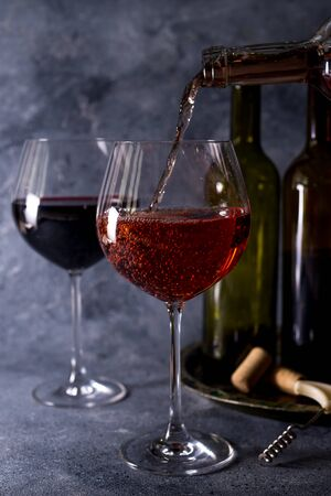 Vin rouge. Bouteille et verre de vin rouge. Style vintage. Vin rouge sur fond noir. Concevez avec un espace pour votre texte.