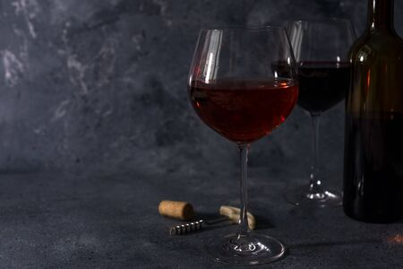 Red wine. Bottle and glass of red wine. Vintage style. Red wine on a black background. Design with space for your text.