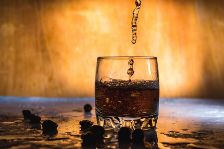 Splash of cold ice in glass of whiskey isolated on a light background Reklamní fotografie