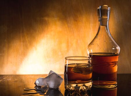 Whiskey with ice cubes. bottle on a wooden table on a wood background A glass of rum alcohol closeup