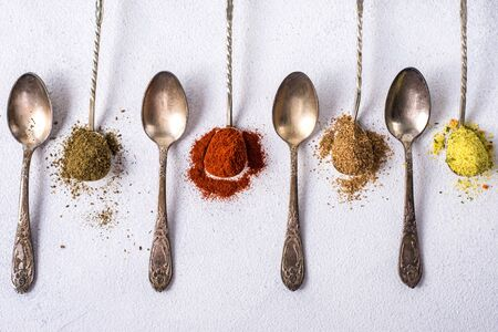 Various spices ground turmeric pepper ginger cinnamon herb seasoning salt paprika caraway seeds on the table. View from above. fragrant indian spices Stock Photo
