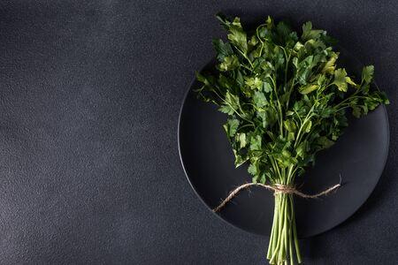 a bunch of fresh healthy parsley on a dark background that plate Fresh raw parsley