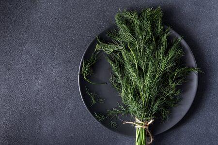 a bunch of fresh healthy dill on a dark background on a plate Fresh raw dill