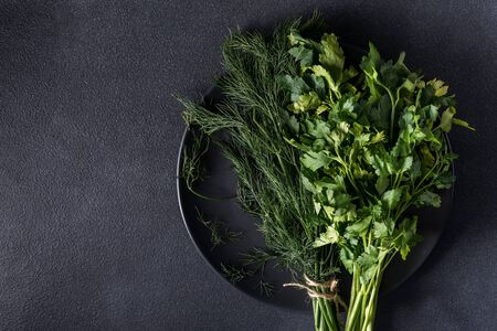 a bunch of fresh healthy greens of parsley and dill on a dark background that plate Fresh parsley and raw dill Zdjęcie Seryjne