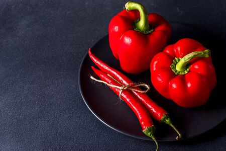 red sweet and hot chili peppers on a dark background with place for text