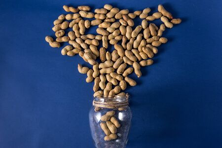 A pile of roasted peanuts on a trendy blue background with place for design and your text. concept. agriculture