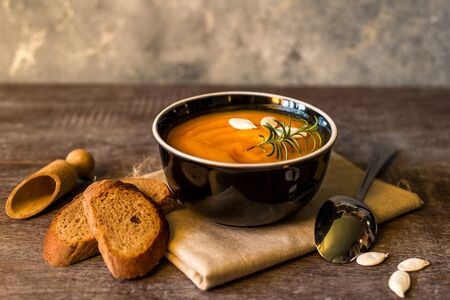 healthy cream of pumpkin soup on a rustic wooden table. Autumn pumpkin cream soup with rosemary herbs and croutons. Copy space