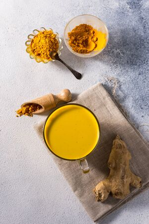 Golden turmeric milk on the white background with spices cinnamon and ingredients Stok Fotoğraf