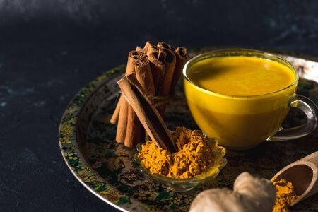 Golden turmeric milk on the dark background with spices cinnamon and ingredients