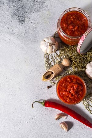 Traditional mexican, georgian and arabic harissa pepper paste on a white concrete background. Useful spicy food Stok Fotoğraf