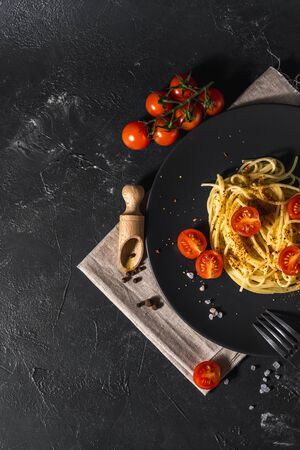 fragrant Italian spaghetti pasta with tomato sauce and cheese and healthy spices served on a dark background Top view.