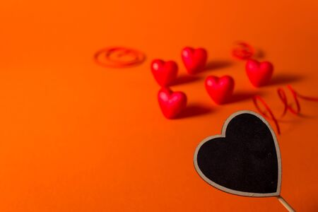 Valentines day romantic abstract satin hearts and ribbon background. Red orange background with hearts