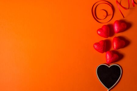 Valentine's day romantic abstract satin hearts and ribbon background. Red orange background with hearts
