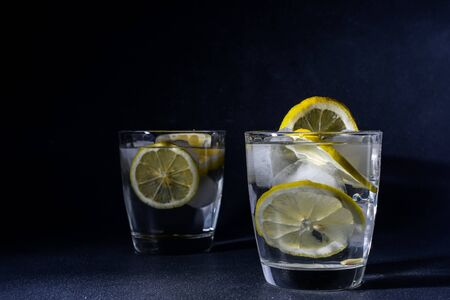Gin and tonic cocktail with lemon slices Ice cube falls into water with lemon Copy space, lemonade