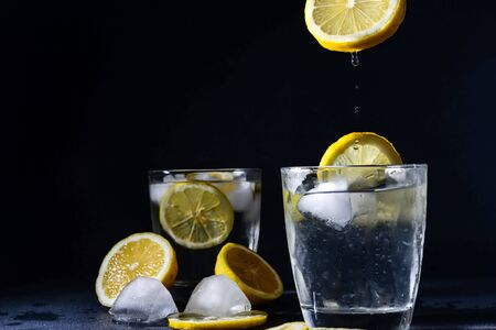 splash Gin and tonic cocktail with lemon slices Ice cube falls into water with lemon Copy space, lemonade