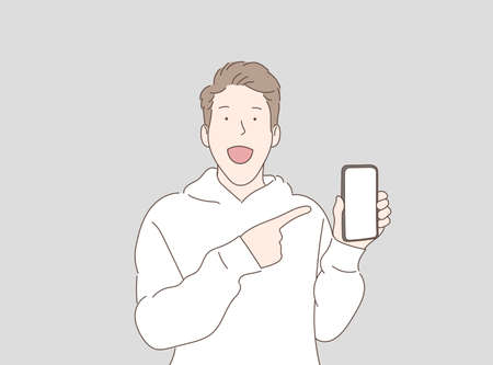 The young man stood looking at the camera with a surprised face and pointed his finger at the white screen of the smartphone he was holding