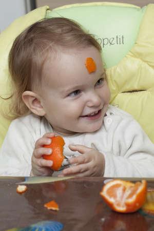 Baby eating mandarins Stock Photo - 11969079