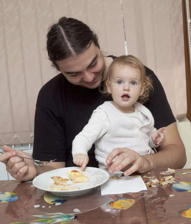 Man feeding a baby with pasta in home photo