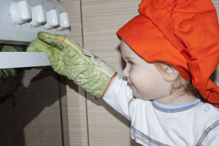 Baby with gloves and hat is opening the oven