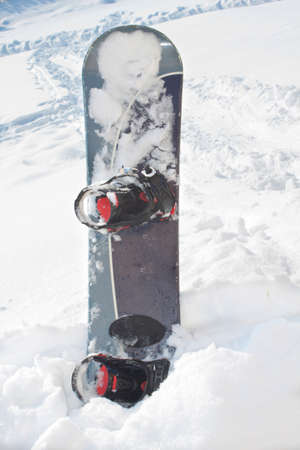 Lone snowboard equipment in white snow photo