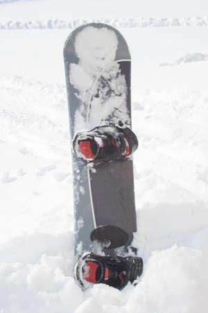 Lone snowboard equipment in white snow photo
