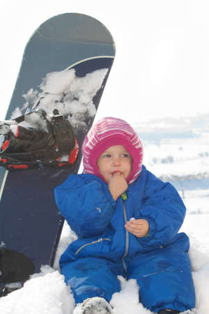 Baby sitting on the snow in front of a snowboard