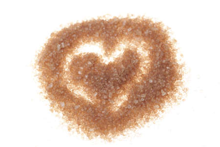 Brown sugar heart isolated on white photo
