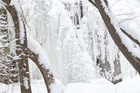 Frozen waterfall in a forest. Landscape nature shot. Stock Photo