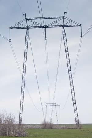 Big power pole in green field photo