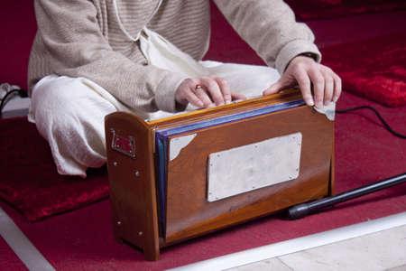 follower: Krishna follower plays harmonium indoor Stock Photo
