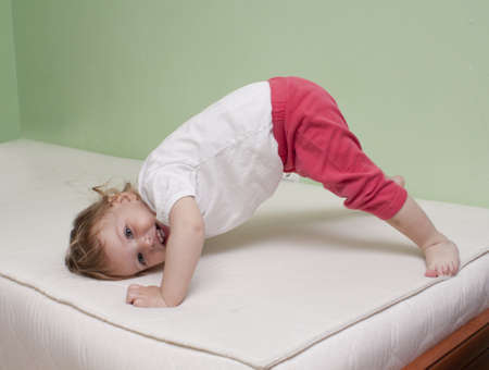 Baby practice yoga on bed photo