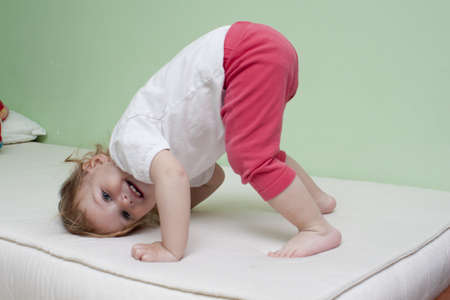 Baby practice yoga on bed Stock Photo