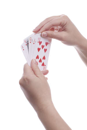 Womans hands holding playing cards. Royal flush. Isolated. photo