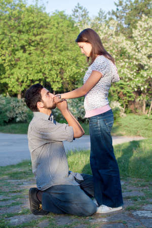 Young man propose to his girlfriend on knee photo