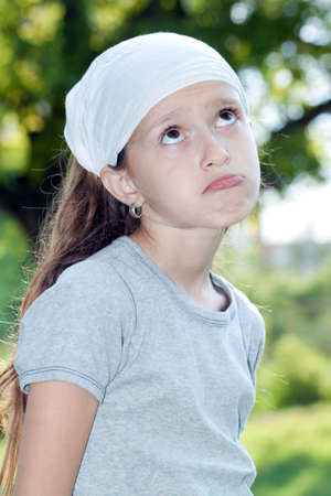 Little girl looking sad in a park photo