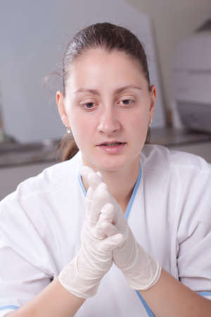 Woman putting gloves in laboratory environment photo