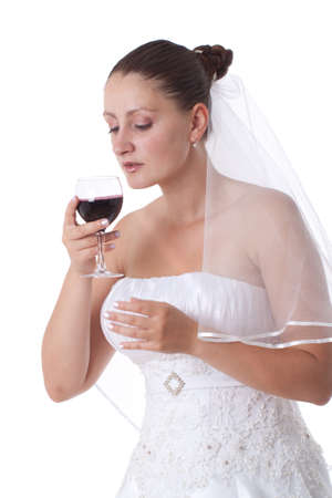 Bride in white holding a glass full of red wine. Isolated.