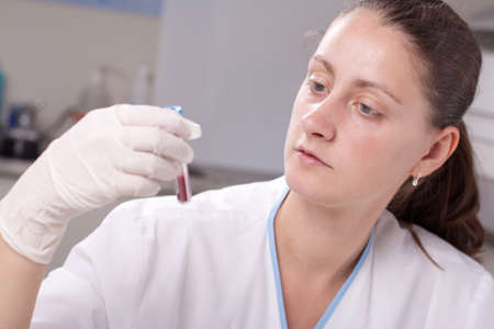 Woman holding test tube full of blood in laboratory environment