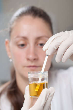 Woman making urine test with ph material in laboratory