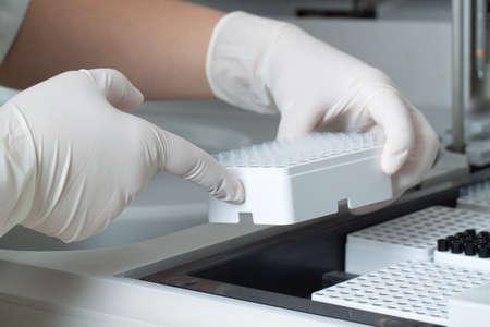analyzer: Woman loading simples in biochemical analyzer. Laboratory equipment.