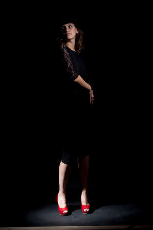Woman with red shoes. Studio shot.