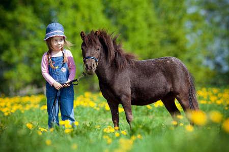 femme a cheval: Des enfants et petit cheval dans le domaine au printemps.