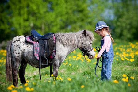 kinderen: Kind en klein paard in het veld in de lente.