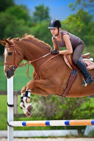 caballo saltando: Salto de niña con el castaño de indias Foto de archivo