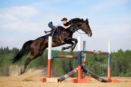 caballo saltando: Niña saltando con el caballo de la bahía