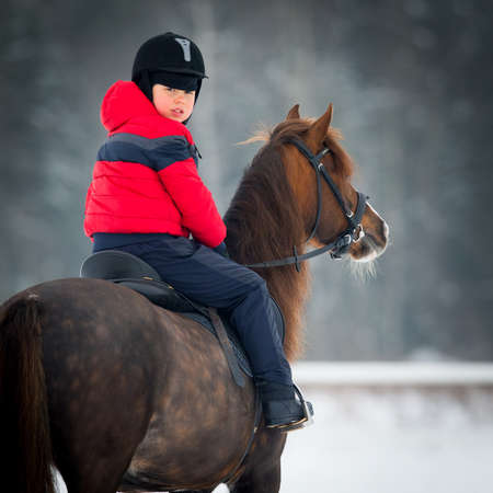 riding horse: Small boy with a horse in winter - horse riding