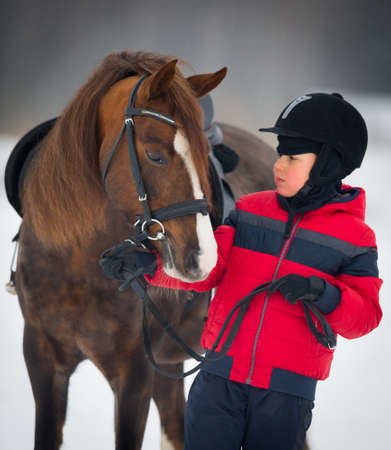 Small boy with a horse in winter - horse riding photo