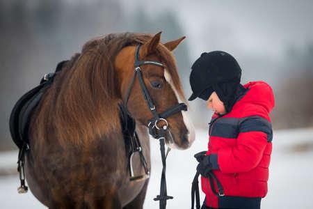 Piccolo ragazzo con un cavallo in inverno - equitazione Archivio Fotografico - 23477678