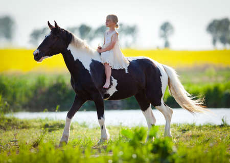 Child riding a horse in filed